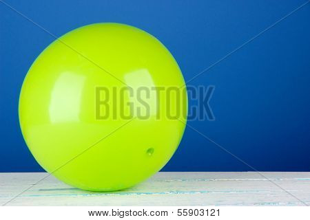 Bright green ball on table on blue background