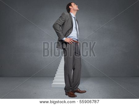 Smiling businessman with hands on hips against shut door at top of steps