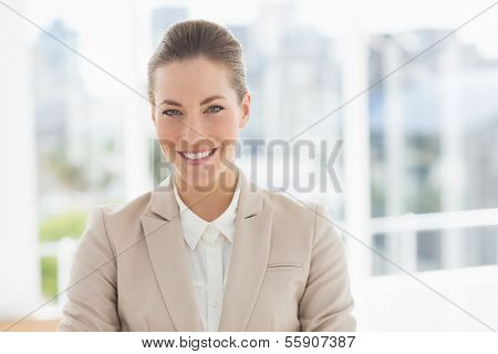 Close-up portrait of a young businesswoman smiling in a bright office