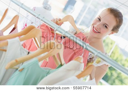 Close-up portrait of happy female customer selecting clothes at clothing rack in store