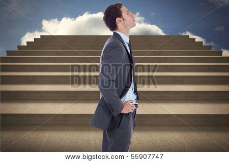 Serious businessman with hands on hips against steps against blue sky