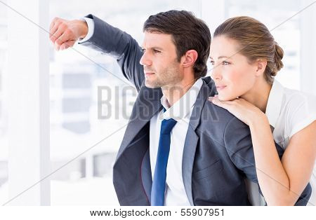 Side view of a smartly dressed business couple looking away in a bright office