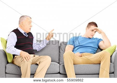 Father reprimending his son seated on a modern sofa isolated on white background