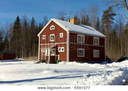 Red Wooden House In Snowlandscape