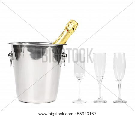 Bottle of champagne in cooler and three glasses.