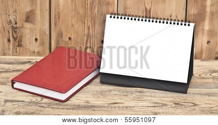 desk calendar with red leather note book on wood table