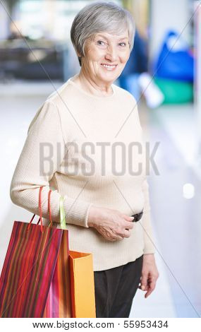 Portrait of happy woman with paperbags looking at camera in the mall