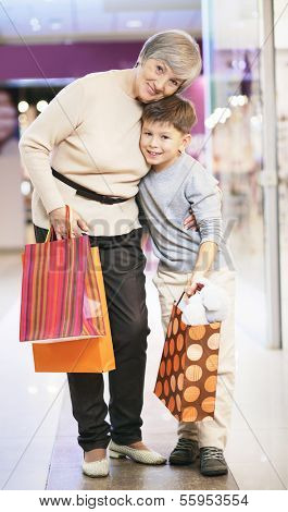 Portrait of happy child and his grandmother with paperbags looking at camera