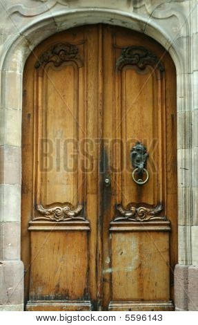 Old wooden door with ornament and original metal handle in a cathedral in Strasbourg, France.