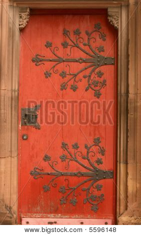 Old red door with metal ornament in a cathedral in Strasbourg