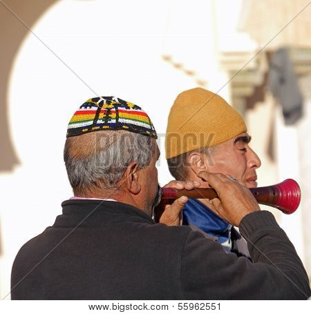 Close up of two traditional Moroccan musicians in square