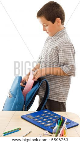 Schoolboy Putting An Exercise Book In The Schoolbag