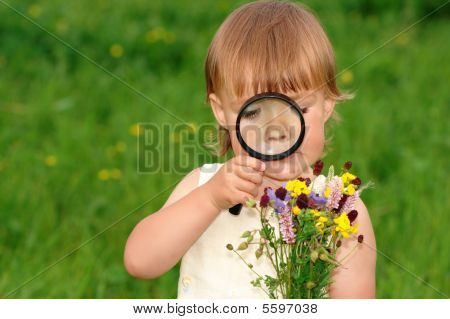 Child Looking At Flowers Through Magnifying Glass