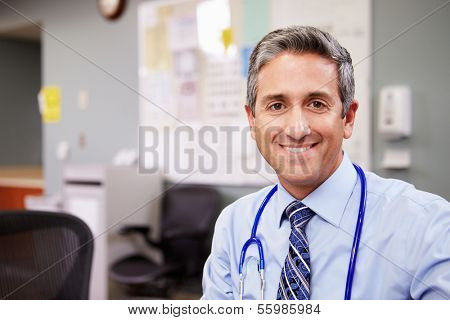 Portrait Of Doctor Working At Nurses Station