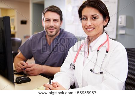 Female Doctor With Male Nurse Working At Nurses Station