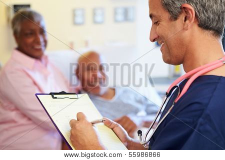 Close Up Of Male Nurse Updating Patient Notes
