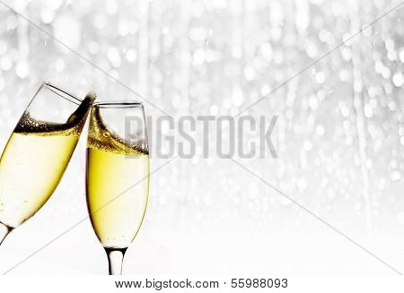 Glasses with champagne on light silver background