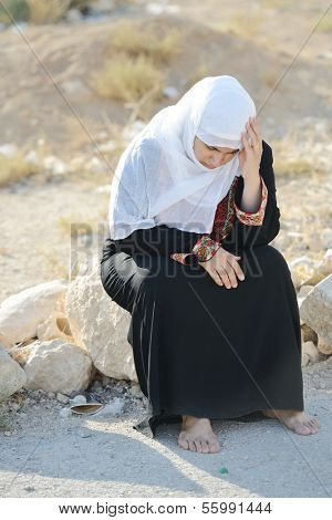 Desperate Arabic woman sitting on rock and crying