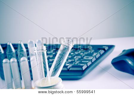 Test Tubes In Laboratory On Table Near Computer Keyboard And Mouse