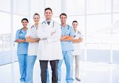 stock photo of surgeons  - Portrait of confident happy group of doctors standing at the medical office - JPG