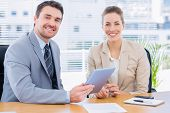 stock photo of half-dressed  - Smartly dressed young man and woman in a business meeting at office desk - JPG