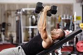 stock photo of chest  - Athletic young man laid on back working his chest with heavy dumbbells - JPG
