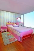 stock photo of girly  - Small modern children girly pink bedroom interior - JPG