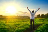 stock photo of rapture  - happy man with hands up on sunset background - JPG