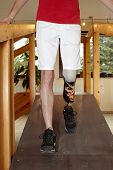 foto of amputee  - Male prosthesis wearer with lower leg amputation training to walk in a special parcour or interior area where surfaces have been laid out to simulate realistic environmental situations - JPG