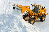 stock photo of excavator  - Excavator is clearing the streets after snow drifts - JPG