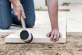 image of bricklayer  - Man hitting the concrete slab with a rubber hammer - JPG
