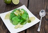 image of jello  - Portion of Lime Jello with freh fruits on wooden background - JPG