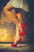 stock photo of short legs  - woman legs in red high heel shoes and short skirt outdoor shot against old metal door - JPG