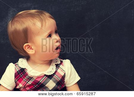 frightened baby girl pupil with chalk at school board