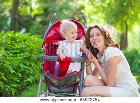 Beautiful Young Woman With Her Child In A Baby Carriage