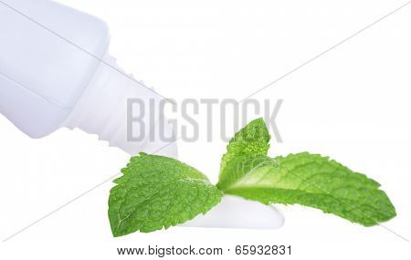 Toothpaste squeezed from tube, mint leaves, close-up, isolated on white