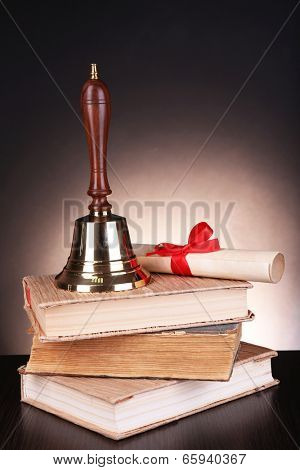 Gold retro school bell with books on table on dark background