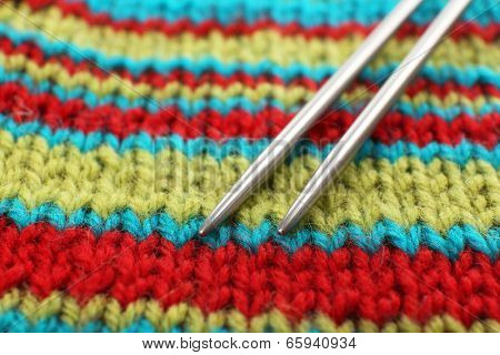 Two knitting spokes and knitted fabric close up