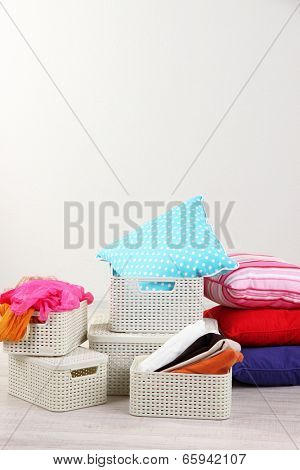 Plastic baskets with things in floor on room background