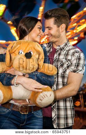 Romantic couple at amusement park, smiling and looking at each other