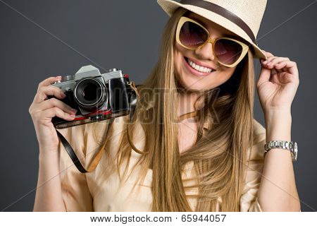 Smiling tourist girl with  photo camera and sunglasses