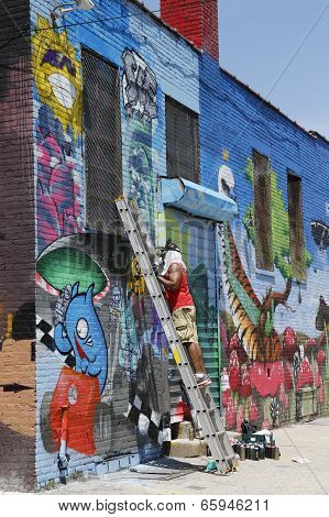 Street artist painting mural at Williamsburg in Brooklyn