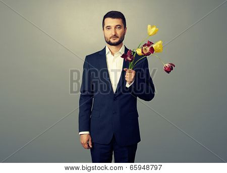 handsome man with faded flowers over dark background