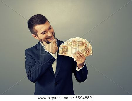 smiley businessman looking at money and thinking about something over dark background