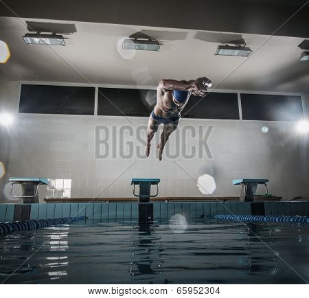 Young muscular swimmer jumping from starting block in a swimming pool