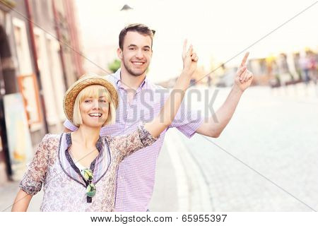 A picture of a young happy couple hailing a taxi in a city