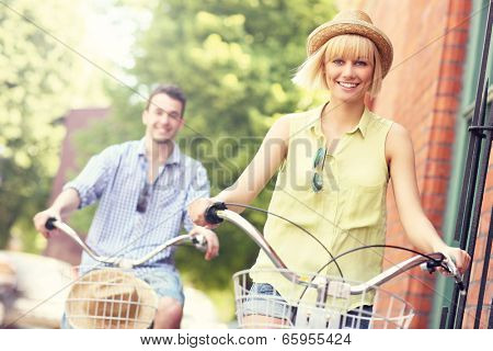 A picture of a young couple cycling in the city