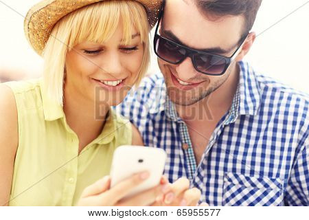 A picture of a young couple using a phone
