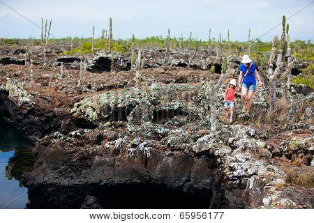 Mother and daughter walking at scenic terrain at Los Tuneles, Galapagos islands, Ecuador