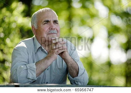 Elderly Man Sitting In The Garden Thinking